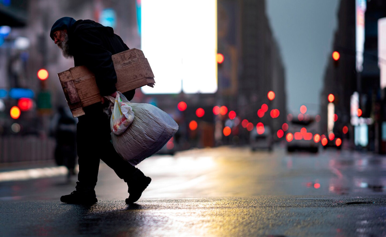 A homeless man carries cardboard as he crosses the almost deserted Times Square in New York on Monday.